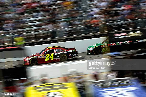 Jeff Gordon driver of the Drive to End Hunger Chevrolet leads Dale Earnhardt Jr driver of the Amp Energy/National Guard Chevrolet during the NASCAR...