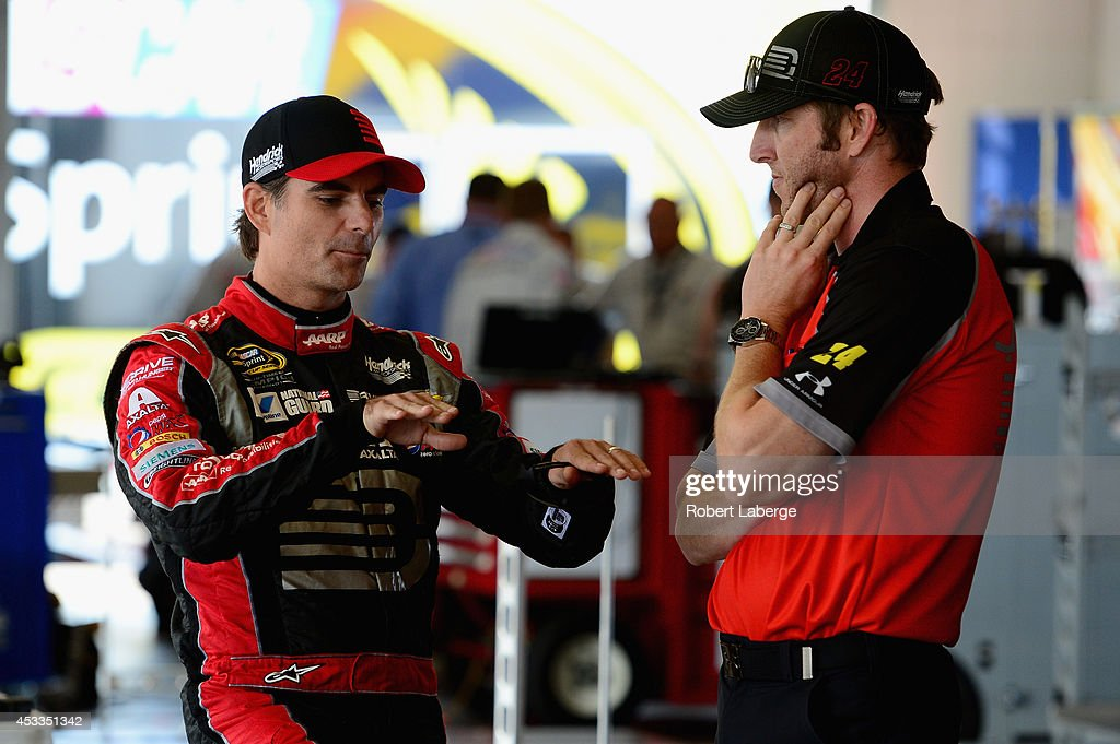 Jeff Gordon driver of the Drive to End Hunger Chevrolet left talks with crew chief Alan Gustafson in the garage area during practice for the NASCAR...