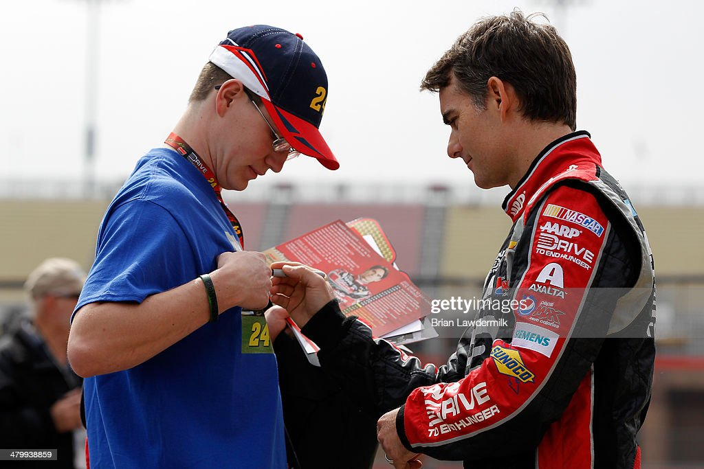 Jeff Gordon, driver of the #24 Drive To End Hunger Chevrolet, signs an autograph for a fan during practice for the NASCAR Sprint Cup Series Auto Club 400 at Auto Club Speedway on March 21, 2014 in Fontana, California.