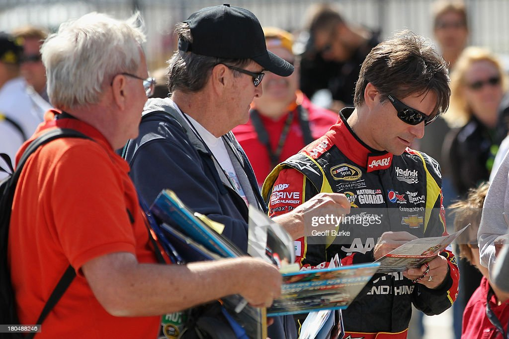 Jeff Gordon, driver of the #24 Drive To End Hunger Chevrolet, signs autographs during practice for the NASCAR Sprint Cup Series Geico 400 at Chicagoland Speedway on September 13, 2013 in Joliet, Illinois.