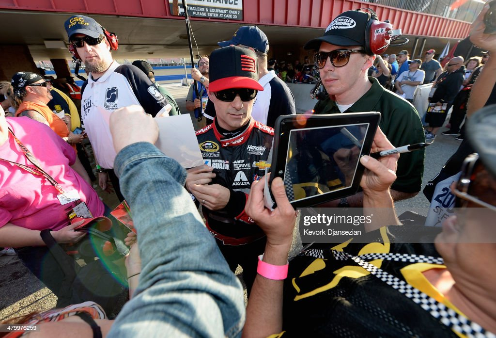 Jeff Gordon, driver of the #24 Drive To End Hunger Chevrolet, signs autographs for fans during qualifying for the NASCAR Sprint Cup Series Auto Club 400 at Auto Club Speedway on March 21, 2014 in Fontana, California.