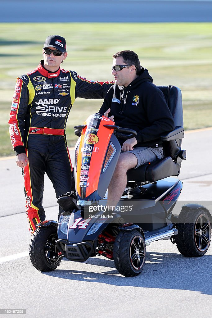 Jeff Gordon, driver of the #24 Drive To End Hunger Chevrolet, speaks with NASCAR driver Tony Stewart during qualifying for the NASCAR Sprint Cup Series Geico 400 at Chicagoland Speedway on September 13, 2013 in Joliet, Illinois.
