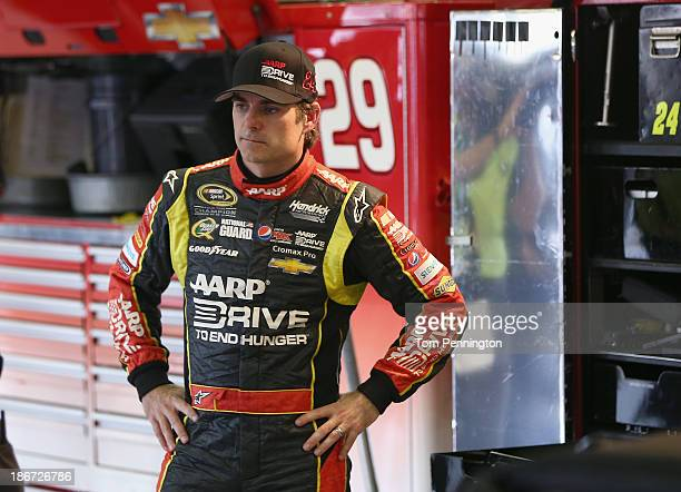 Jeff Gordon driver of the Drive to End Hunger Chevrolet stands in the garage following an incident on track during the NASCAR Sprint Cup Series AAA...