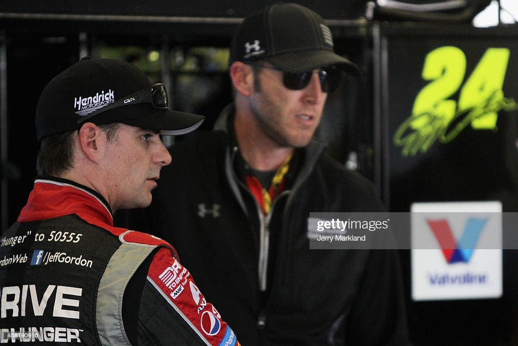 Jeff Gordon driver of the Drive To End Hunger Chevrolet talks to his crew chief Alan Gustafson in the garage area during practice for the NASCAR...