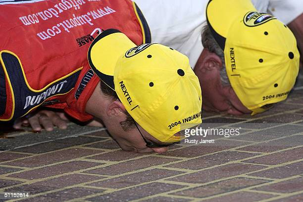 Jeff Gordon driver of the Dupont Chevrolet and team owner Rick Hendrick celebrate by kissing the bricks after winning the NASCAR Nextel Cup series...