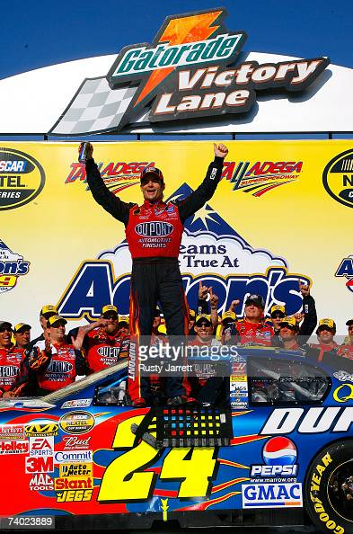 Jeff Gordon driver of the DuPont Chevrolet celebrates with his crew in victory lane after winning the NASCAR Nextel Cup Series Aaron's 499 at...