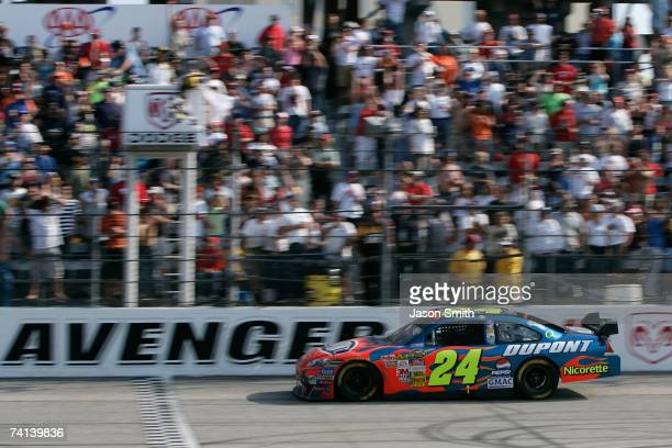 Jeff Gordon driver of the DuPont Chevrolet comes to the finish line to win the NASCAR Nextel Cup Series Dodge Avenger 500 on May 13 2007 at...