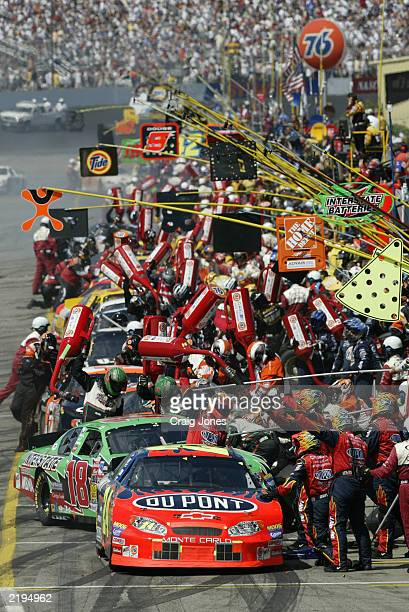 Jeff Gordon driver of the Dupont Chevrolet leads the pack in a pit stop during the New England 300 on July 20 2003 at New Hampshire Int'l Speedway in...