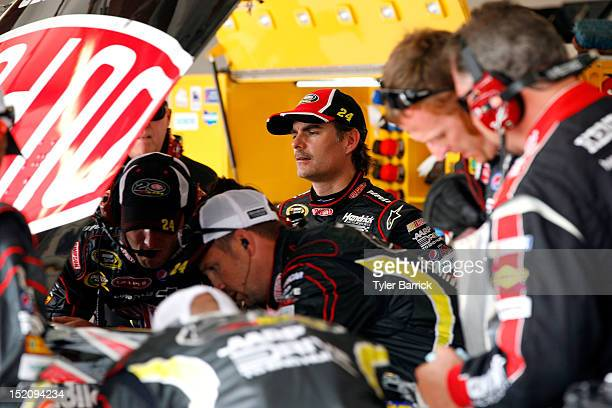 Jeff Gordon driver of the DuPont Chevrolet looks on as crew members work on his car in the garage after it suffered damage when it hit the wall...