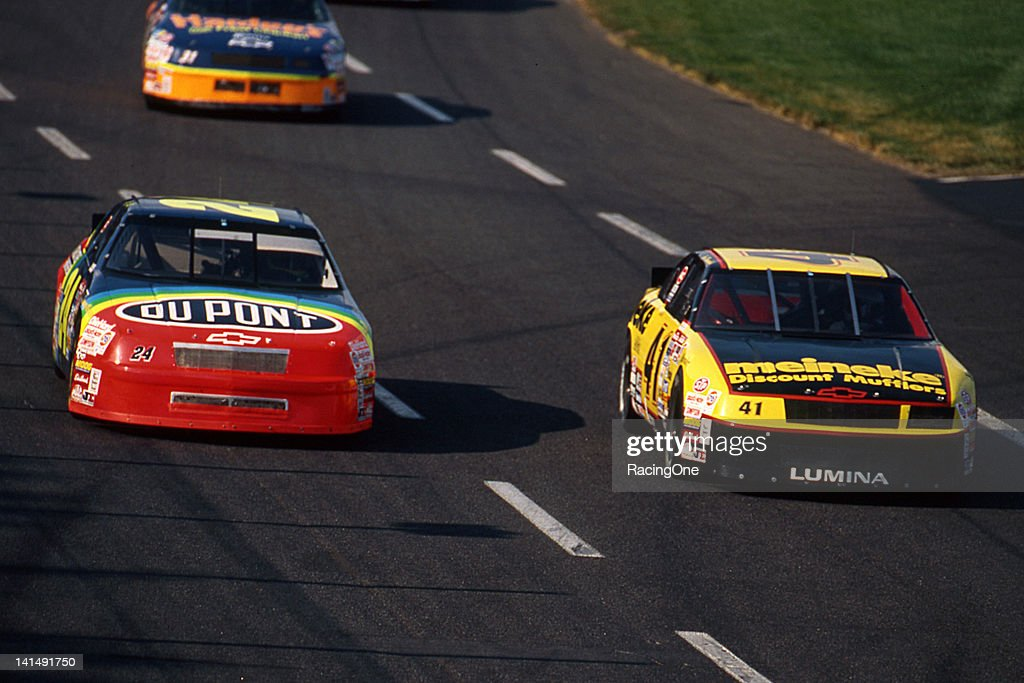 Jeff Gordon driver of the DuPont Chevrolet passes Joe Nemechek driver of the Meineke Chevrolet on his way to winning the NASCAR Cup CocaCola 600 and...