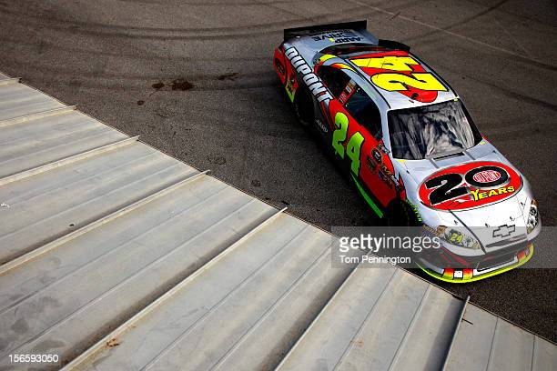 Jeff Gordon drives the DuPont 20 Years Celebratory Chevrolet through the garage during practice for the NASCAR Sprint Cup Series Ford EcoBoost 400 at...