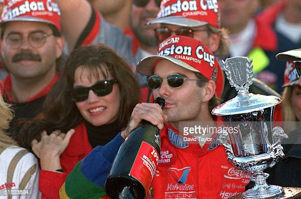 Jeff Gordon of DuPont Chevrolet celebrates in victory lane drinking champagne after winning the Winston Cup championship in the NASCAR NAPA 500 at...