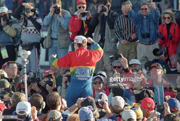 Jeff Gordon of DuPont Chevrolet celebrates winning the Winston Cup championship in the NASCAR NAPA 500 at the Atlantic Motor Speedway on November 12...