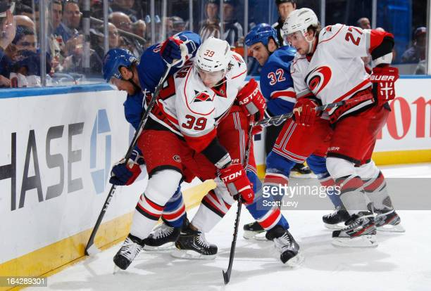 Jeff Halpern and Michael Haley of the New York Rangers battle for the puck against Patrick Dwyer and Justin Faulk of the Carolina Hurricanes at...
