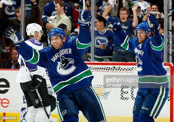 Jeff Halpern of the Los Angeles Kings skates away dejected as Mikael Samuelsson and Henrik Sedin of the Vancouver Canucks celebrate a goal in Game...