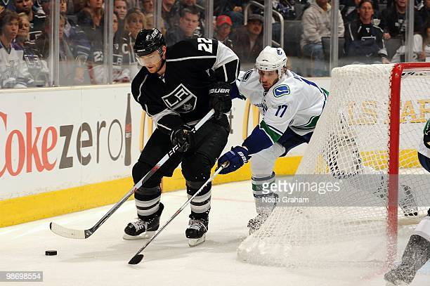 Jeff Halpern of the Los Angeles Kings skates with the puck against Ryan Kesler of the Vancouver Canucks in Game Six of the Western Conference...