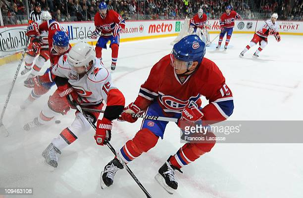 Jeff Halpern of the Montreal Canadiens and Tuomo Ruutu of the Carolina Hurricanes battle for the puck along the boards during the NHL game on...