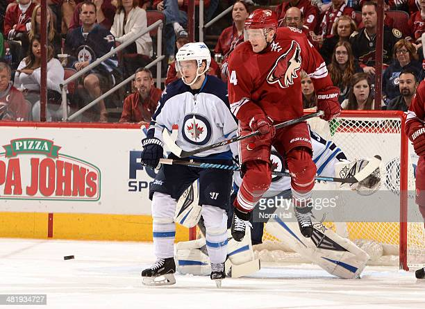 Jeff Halpern of the Phoenix Coyotes attempts to jump over a shot while being defended by Tobias Enstrom of the Winnipeg Jets at Jobingcom Arena on...