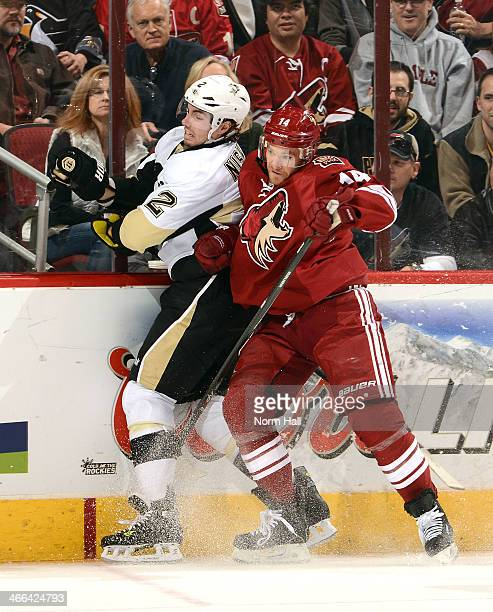 Jeff Halpern of the Phoenix Coyotes checks Matt Niskanen of the Pittsburgh Penguins into the boards at Jobingcom Arena on February 1 2014 in Glendale...