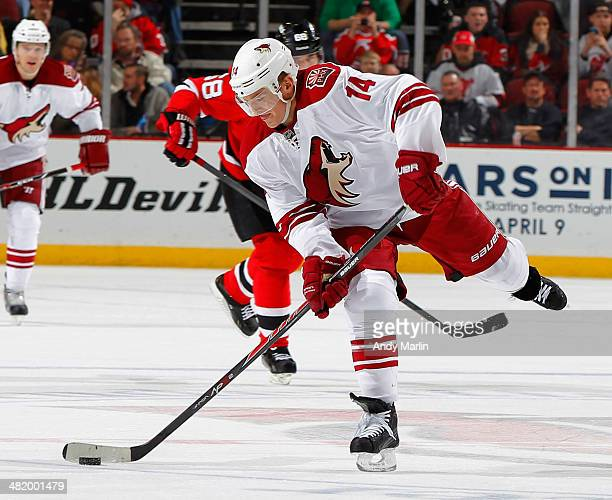 Jeff Halpern of the Phoenix Coyotes controls the puck against the New Jersey Devils at the Prudential Center on March 27 2014 in Newark New Jersey