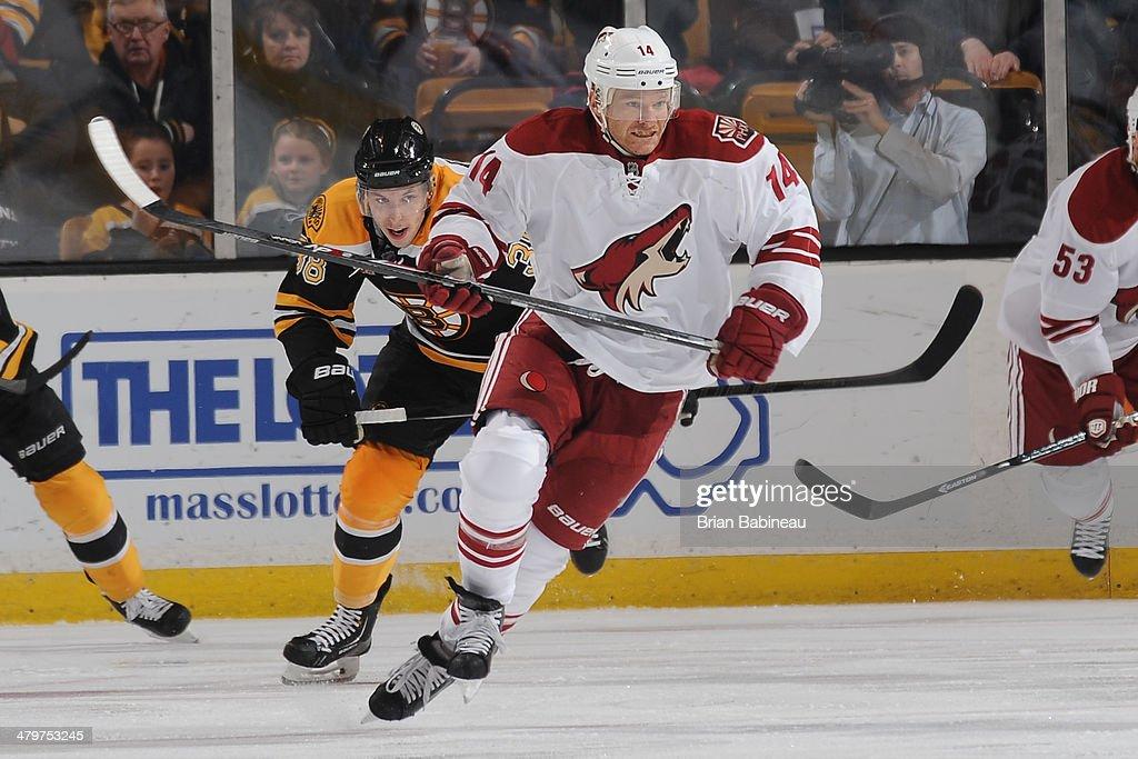 Jeff Halpern of the Phoenix Coyotes skates against Jordan Caron of the Boston Bruins at the TD Garden on March 13 2014 in Boston Massachusetts