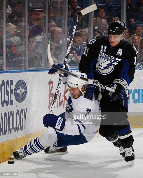 Jeff Halpern of the Tampa Bay Lightning skates around a falling Ian White of the Toronto Maple Leafs for control of the puck during the first period...