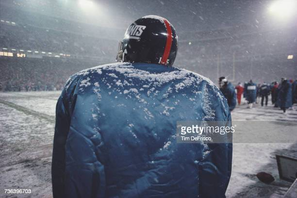 Jeff Hostetlerr backup Quarterback for the New York Giants stands on the sidelines huddled against the falling snow during the National Football...