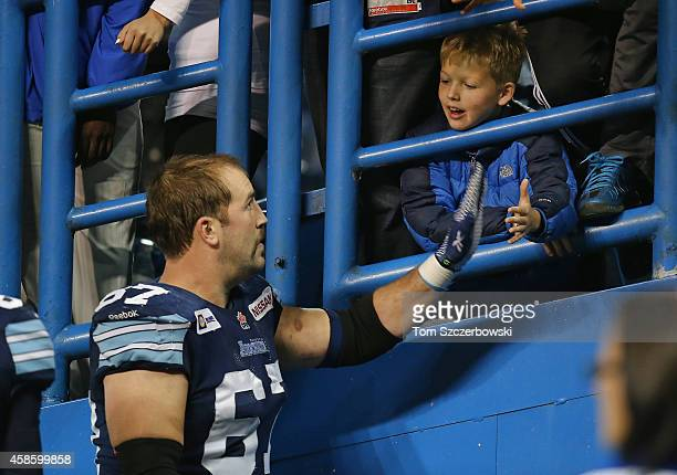 Jeff Keeping of the Toronto Argonauts is congratulated by a young fan after their victory during CFL game action over the Ottawa Redblacks on...