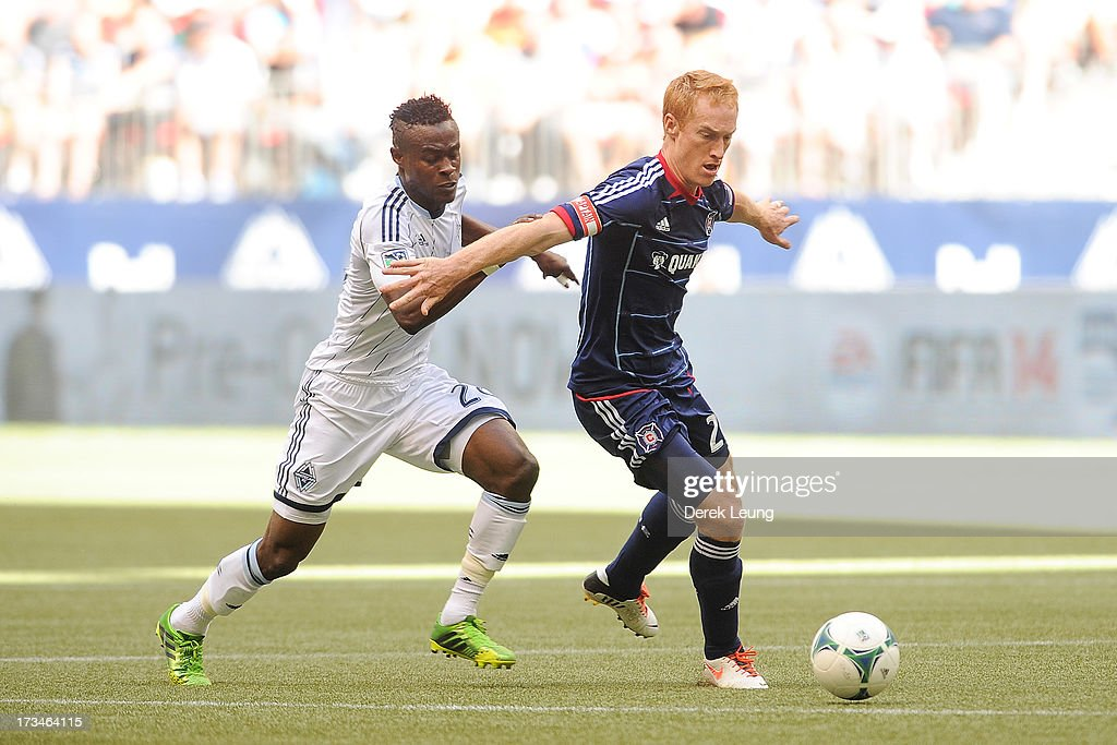 Jeff Larentowicz #20 of Chicago Fire dribbles the ball past Gershon Koffie #28 of the Vancouver Whitecaps during an MLS Match at B.C. Place on July 14, 2013 in Vancouver, British Columbia, Canada.
