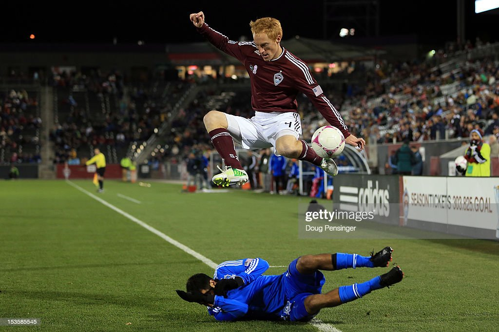 Jeff Larentowicz of the Colorado Rapids leaps over a sliding Steven Beitashour of the San Jose Earthquakes as they battle for control of the ball at...
