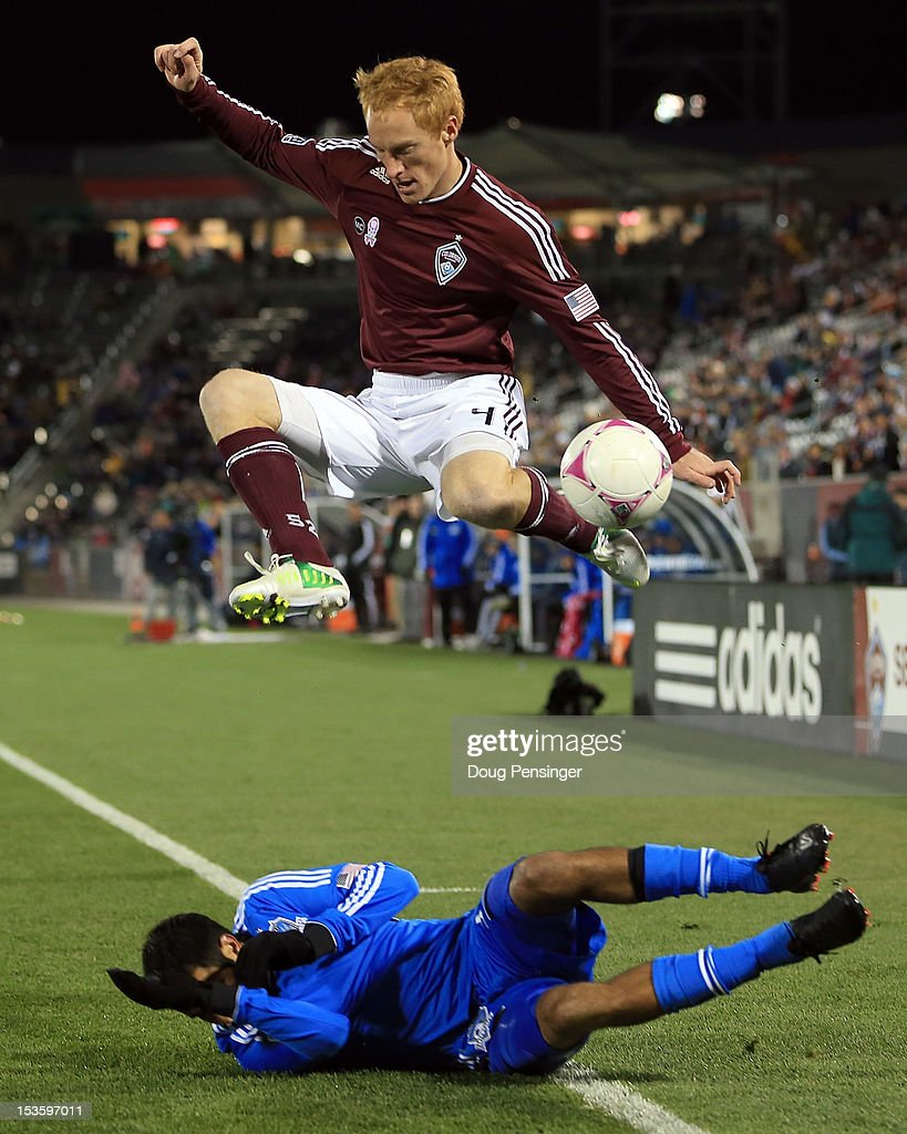 Jeff Larentowicz #4 of the Colorado Rapids leaps over a sliding Steven Beitashour #33 of the San Jose Earthquakes as they battle for control of the ball at Dick's Sporting Goods Park on October 6, 2012 in Commerce City, Colorado. The Earthquakes defeated the Rapids 4-1.