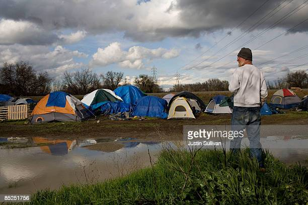Jeff Latchaw a homeless man looks at a pool of water from a recent rain storm at a homeless tent city March 4 2009 in Sacramento California The tent...