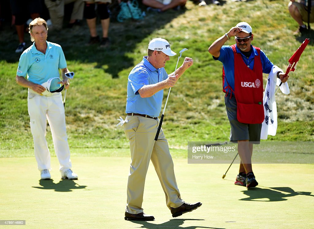 Jeff Maggert of the United States reacts to his final putt for victory with caddie Rusty Uresti and in front of Bernhard Langer of Germany on the...