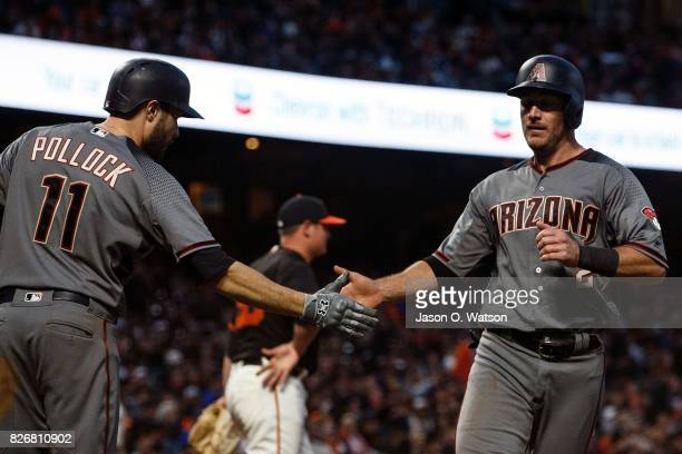 Jeff Mathis of the Arizona Diamondbacks is congratulated by AJ Pollock after scoring a run against the San Francisco Giants during the sixth inning...