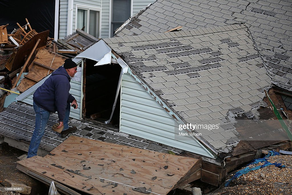 Jeff Mccue looks into the roof to his brothers beach house that was completely demolished by Superstorm Sandy on November 25, 2012 in Ortley Beach, New Jersey. New Jersey Gov. Christie estimated that Superstorm Sandy cost New Jersey $29.4 billion in damage and economic losses.