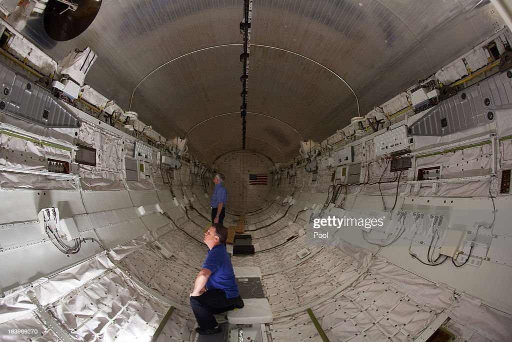 Jeff Moore (foreground) and Dennis R. Jenkins take measurements inside space Shuttle Endeavour's payload bay, celebrating the one year anniversary of Endeavour's journey through the street of Los Angeles, on October 10, 2013 in Los Angeles, California. Lynda Oschin, whose foundation helped to bring the shuttle to Los Angeles, formed the Mr. and Mrs. Samuel and Lynda Oschin Foundation, formed in honor of Oschin's late husband, a Los Angeles businessman and philanthropist.