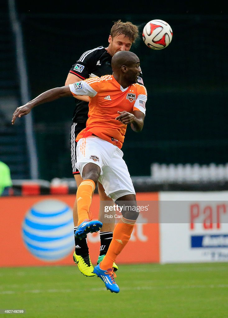 Jeff Parke of DC United and Omar Cummings of Houston Dynamo go up for the ball during the first half at RFK Stadium on May 21 2014 in Washington DC