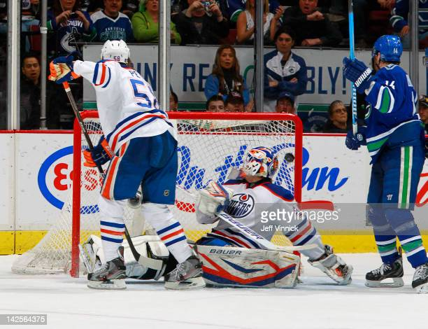 Jeff Petry of the Edmonton Oilers and Alex Burrows of the Vancouver Canucks watch the puck go behind Devan Dubnyk of the Oilers for a goal during...