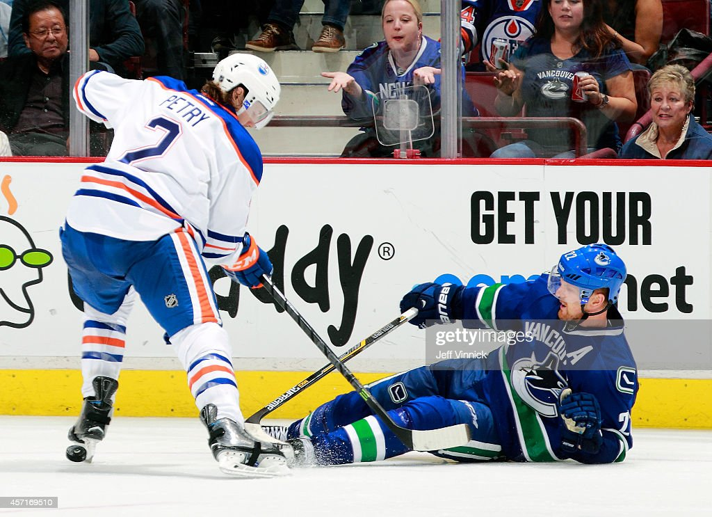Jeff Petry of the Edmonton Oilers checks Daniel Sedin of the Vancouver Canucks to the ice during their NHL game at Rogers Arena October 11 2014 in...