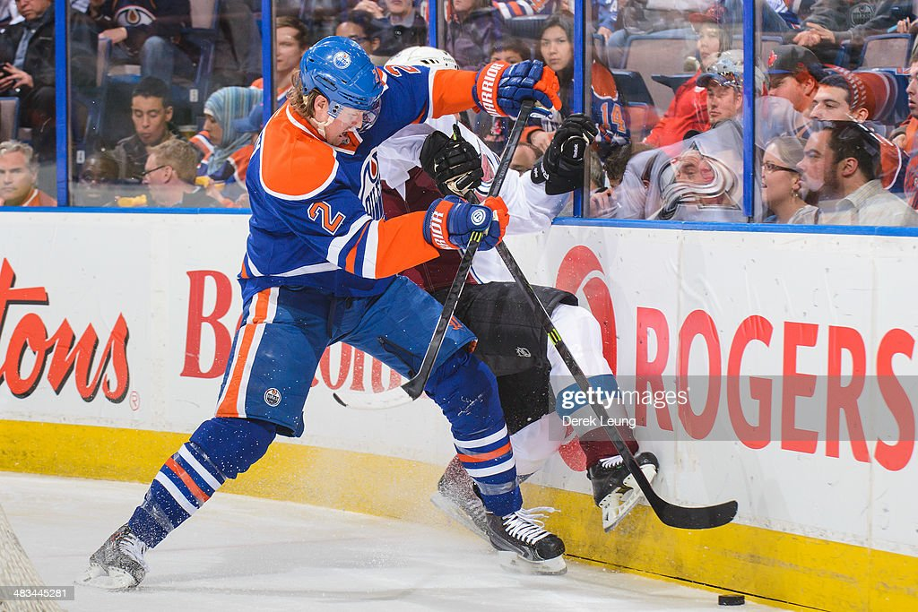 Jeff Petry of the Edmonton Oilers checks Erik Johnson of the Colorado Avalanche during an NHL game at Rexall Place on April 8 2014 in Edmonton...