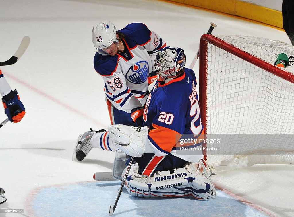 Jeff Petry #58 of the Edmonton Oilers crashes into Goaltender <a gi-track='captionPersonalityLinkClicked' href=/galleries/search?phrase=Evgeni+Nabokov&family=editorial&specificpeople=171380 ng-click='$event.stopPropagation()'>Evgeni Nabokov</a> #20 of the New York Islanders at Nassau Veterans Memorial Coliseum on December 31, 2011 in Uniondale, New York. The Islanders defeat the Oilers 4-1.
