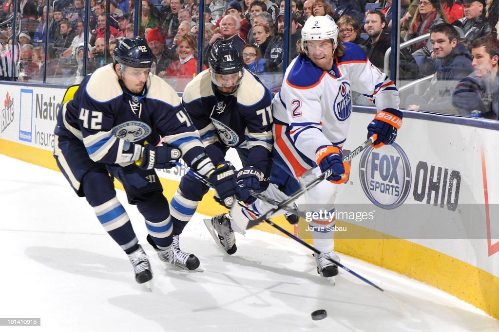 Jeff Petry #2 of the Edmonton Oilers flips the puck up ice as <a gi-track='captionPersonalityLinkClicked' href=/galleries/search?phrase=Artem+Anisimov&family=editorial&specificpeople=543215 ng-click='$event.stopPropagation()'>Artem Anisimov</a> #42 of the Columbus Blue Jackets and <a gi-track='captionPersonalityLinkClicked' href=/galleries/search?phrase=Nick+Foligno&family=editorial&specificpeople=537821 ng-click='$event.stopPropagation()'>Nick Foligno</a> #71 of the Columbus Blue Jackets apply defensive pressure on February 10, 2013 at Nationwide Arena in Columbus, Ohio. Edmonton defeated Columbus 3-1.