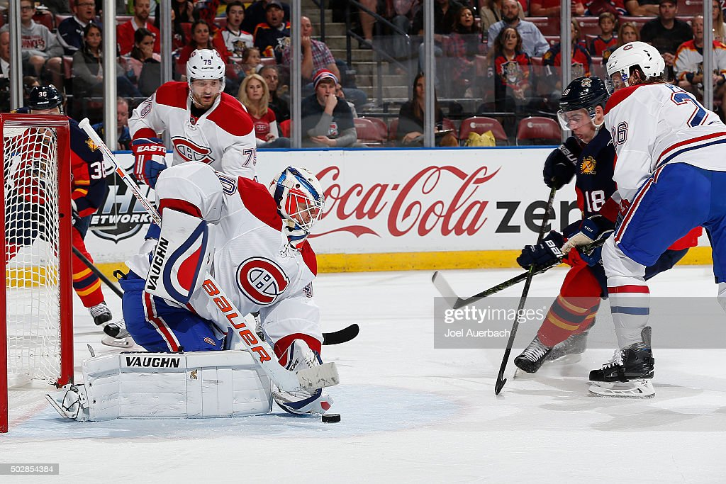 Jeff Petry #26 of the Montreal Canadiens checks Reilly Smith #18 of the Florida Panthers as Goaltender Ben Scrivens #40 stops his shot at the BB&T Center on December 29, 2015 in Sunrise, Florida. The Panthers defeated the Canadiens 3-1.