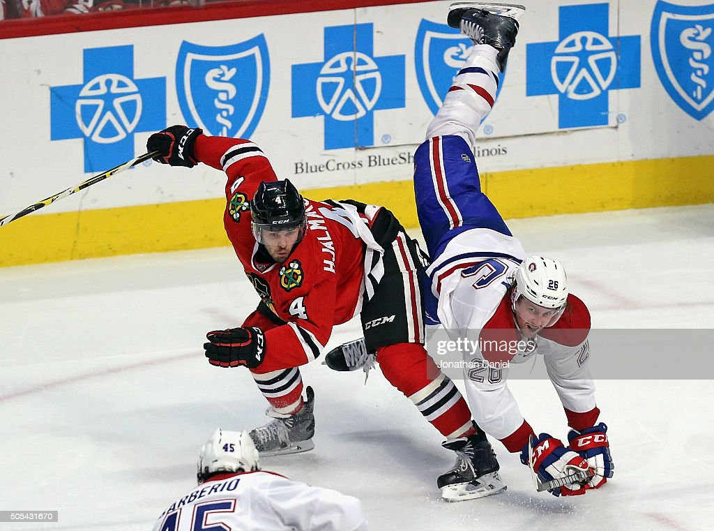 Jeff Petry of the Montreal Canadiens falls over the back of Niklas Hjalmarsson of the Chicago Blackhawks at the United Center on January 17 2016 in...