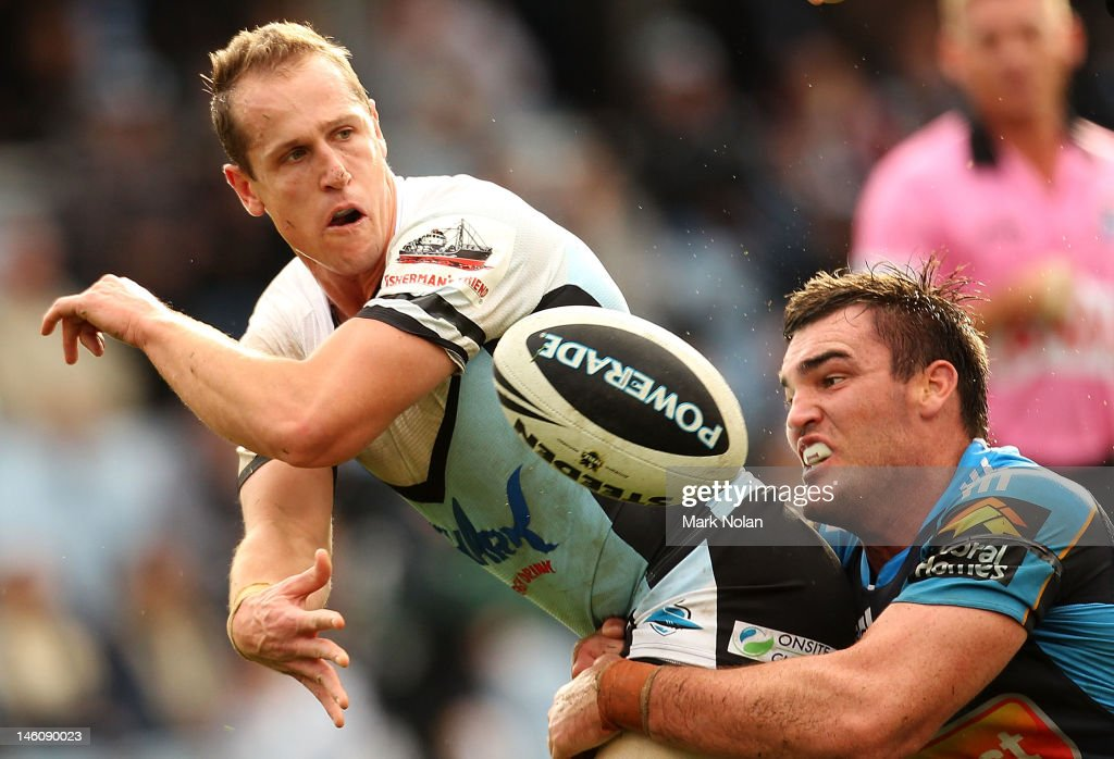 Jeff Robson of the Sharks offloads for Jeremy Smith to score during the round 14 NRL match between the Cronulla Sharks and the Gold Coast Titans at...