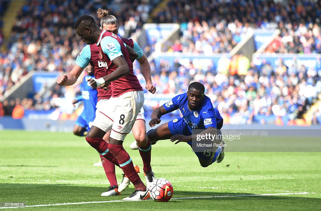 Jeff Schlupp of Leicester City goes over under the challenge of Andy Carroll of West Ham United during the Barclays Premier League match between...