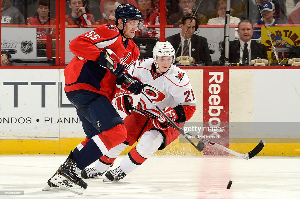 Jeff Schultz #55 of the Washington Capitals and <a gi-track='captionPersonalityLinkClicked' href=/galleries/search?phrase=Drayson+Bowman&family=editorial&specificpeople=4111563 ng-click='$event.stopPropagation()'>Drayson Bowman</a> #21 of the Carolina Hurricanes chase the puck at the red line during an NHL game at Verizon Center on March 12, 2013 in Washington, DC.
