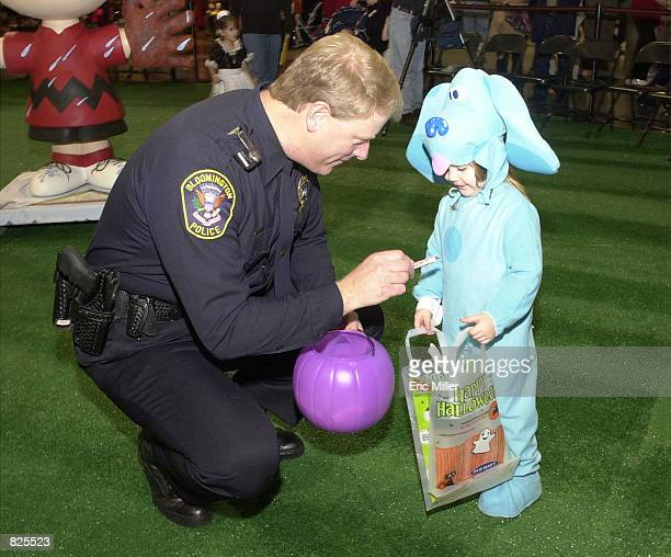 Jeff Schwiesow an officer with the Bloomington Minnesota Police Department gives some candy to a trickortreater October 31 2001 at the Mall of...
