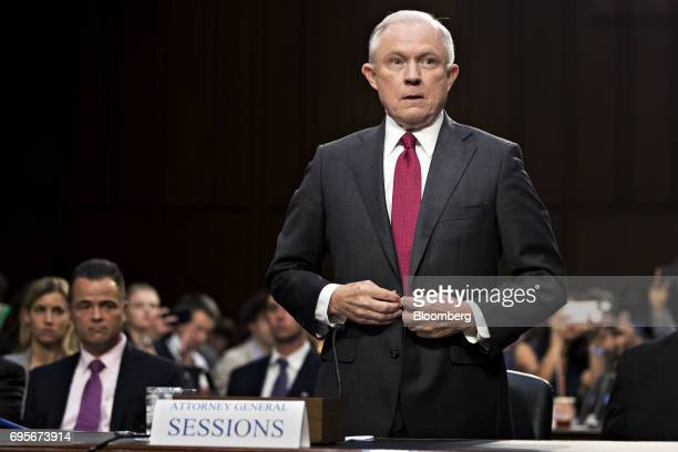 Jeff Sessions US attorney general buttons his jacket before swearing in to a Senate Intelligence Committee hearing in Washington DC US on Tuesday...