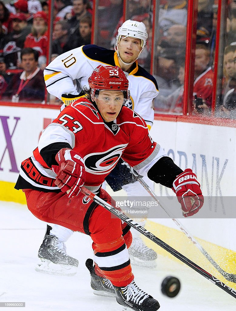 Jeff Skinner #53 of the Carolina Hurricanes and Christian Ehrhoff #10 of the Buffalo Sabres chase a loose puck along the boards during play at PNC Arena on January 24, 2013 in Raleigh, North Carolina.